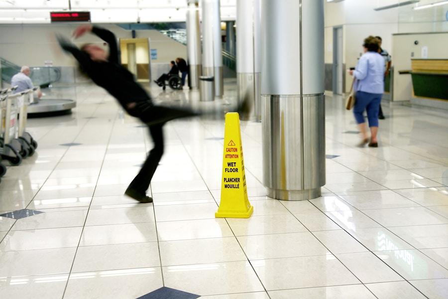 man slip and fall next to sign on floor