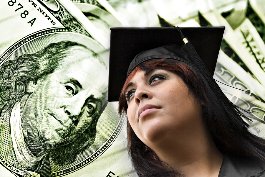 woman with graduation cap and money bills
